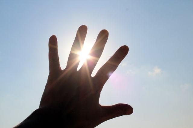 キラキラ輝く太陽に手をかざす