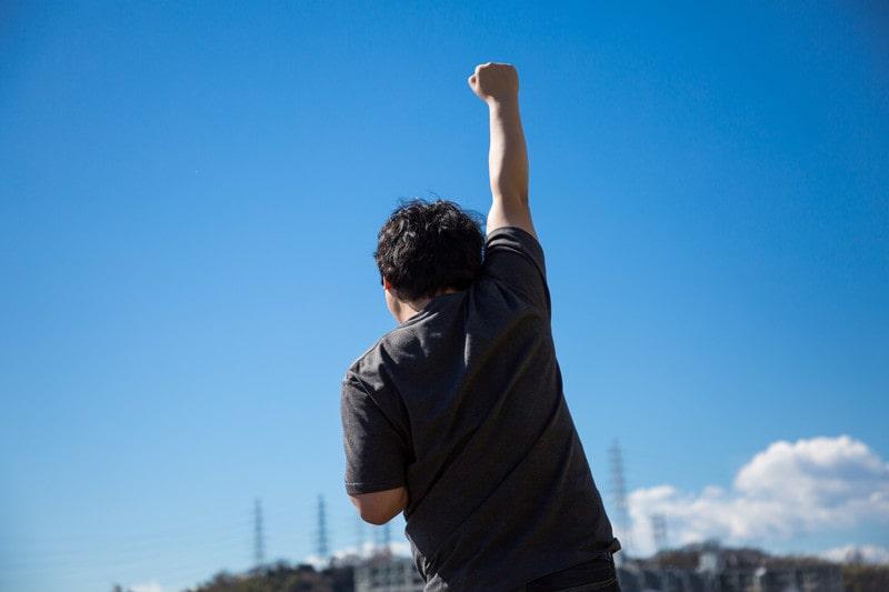 青空の下でガッツポーズをする男性