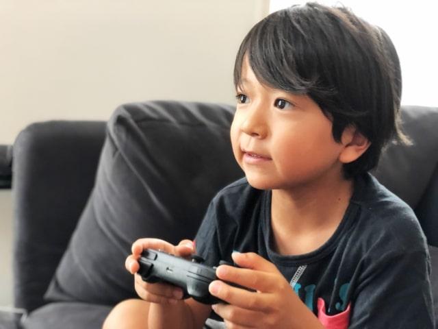 リビングでゲームをする少年