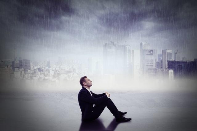 雨の降る都会の風景と三角座りのスーツの男性