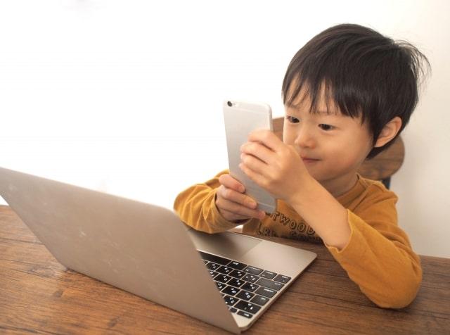 スマホとパソコンを見て楽しむ男の子