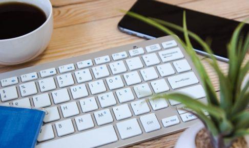机の上に置いてあるキーボードとコーヒーと観葉植物